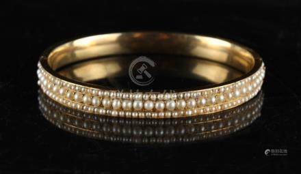 An unmarked yellow gold (tests 15ct) hinged bracelet, set with three rows of seed pearls,