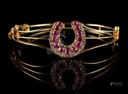 An 18ct yellow gold ruby & diamond hinged bracelet, of openwork design with horseshoe shaped panel