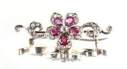 A Belle Epoque ruby & diamond floral brooch, the five petals set with a cut ruby flanked by pave set