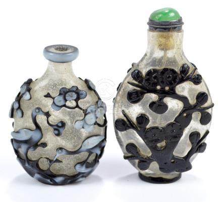 A Chinese double overlay white and black glass snuff bottle of flat ovoid form decorated with a