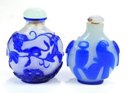Two Chinese blue carved overlay glass snuff bottles of flat globular forms,