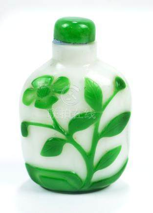 A Chinese Peking green and white carved overlay glass snuff bottle of flat ovoid form decorated
