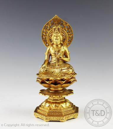 A gilt metal figure of a Bodhisattva seated upon a lotus throne, modelled in the mudra position,