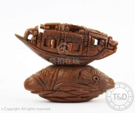 A Chinese carved coquilla nut modelled as a junk,