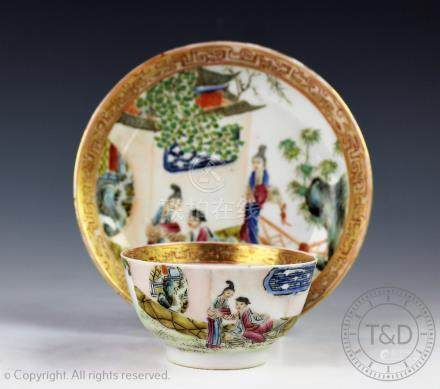 An 18th century style tea bowl and saucer, each decorated with figures on a veranda,
