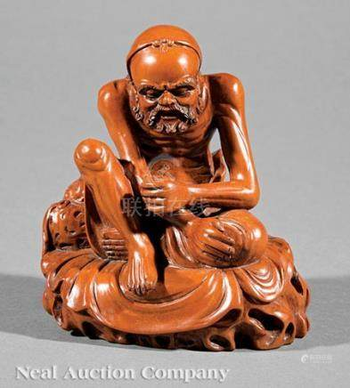 Chinese Huangyang or Boxwood Louhan, Qing Dynasty (1644-1911), carved seated on rockwork beside a