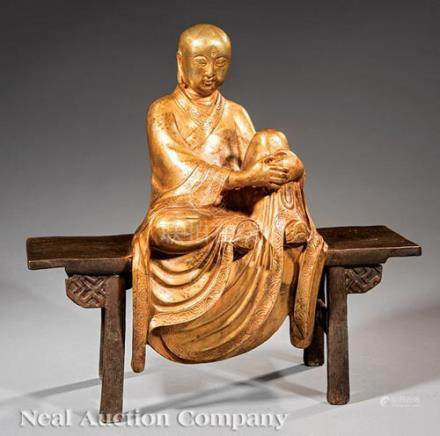 Chinese Gilt and Patinated Bronze Luohan, 20th c., modeled seated on a long table wearing long loose