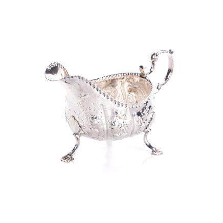 AN IRISH SILVER SAUCE BOAT, MATTHEW WEST, DUBLIN, 1770 the circular body with gadrooned rim