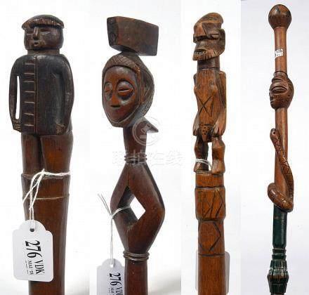 Ensemble de quatre cannes en bois sculpté dont une est polyc