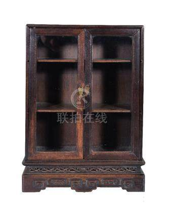 A small Chinese hardwood collector's cabinet, late Qing Dynasty, with two glazed doors, the base