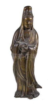 A Chinese gilt-bronze figure of Guanyin, standing holding a scroll, traces of gilding, 26cm high