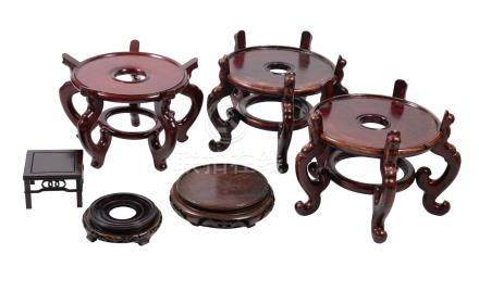 Six various Chinese wood stands, 20th century, comprising a large circular pair supported on five
