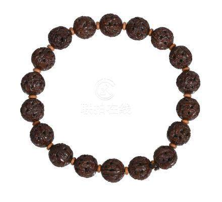 A Chinese 'heidao' nut bead necklace, composed of eighteen carved nuts each approximately 1.6cm