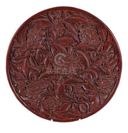 A large Chinese red lacquer tray, in Ming style, of shallow circular form, the interior deeply