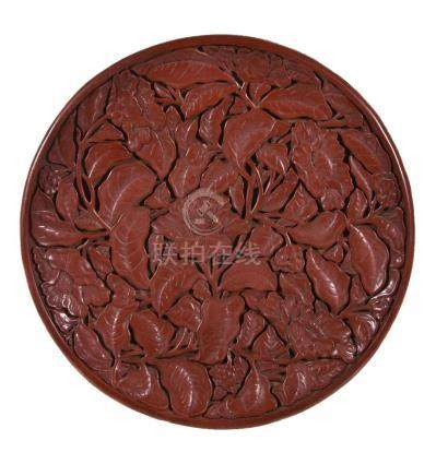 A Chinese cinnabar lacquer dish, in early Ming style, of circular form, the shallow rounded sides