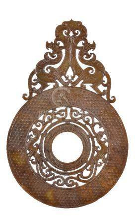 A Chinese Han-style reticulated brown and yellow jade disc, bi, cut with a central openwork of