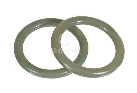 A pair of Chinese green jade bangles, of generally even tone with russet inclusions, 6.9cm