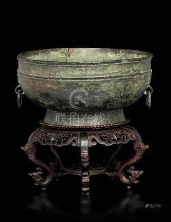 A bronze cup with a Taotie mask along the handles,