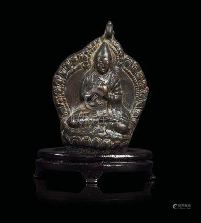 A bronze pendant depicting Lama seated on a lotus