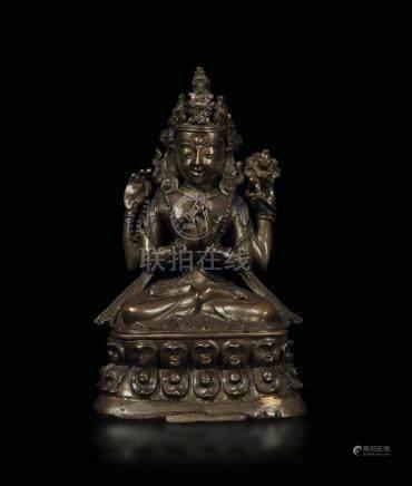 A bronze figure of Shadakshari seated on a double lotus