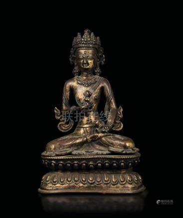 A bronze figure of Avalokitesvara seated on a double