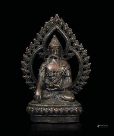 A bronze figure of Buddha Sakyamuni with aura seated on