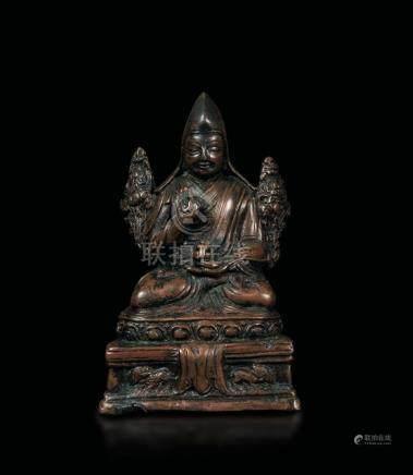 A bronze figure of Lama Tsongkhapa seated on a lotus