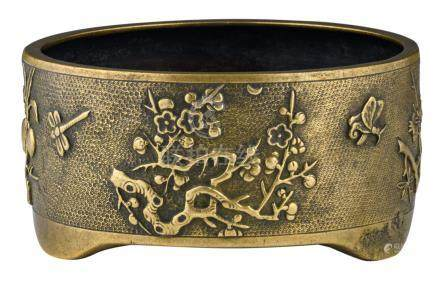 A Chinese bronze relief decorated tripod incense burner with flower branches, butterflies and dragonflies, with a Xuande mark, 17th/18thC, H 8,7 - ø 17,3 cm
