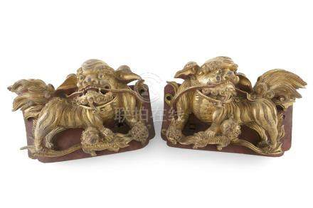 A PAIR OF CHINESE GILT LACQUER CARVED WOOD KYLINS AND CUBS. 29.5cm wide