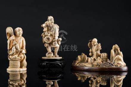 Japanese Art Three ivory Okimono: a group and a pan dealer J
