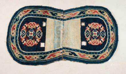 Himalayan Art An oval shaped Tibetan saddle carpet decorated