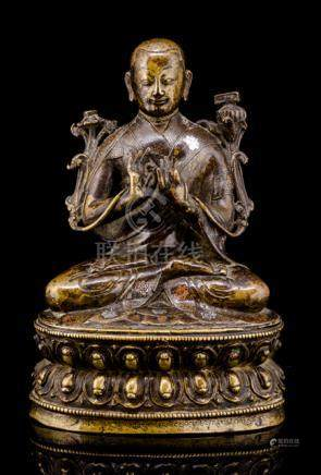 A RARE SILVER- AND COPPER-INLAID BRONZE FIGURE OF BSOD.NAMS.SENGE, TIBET, early 16th ct., seated in