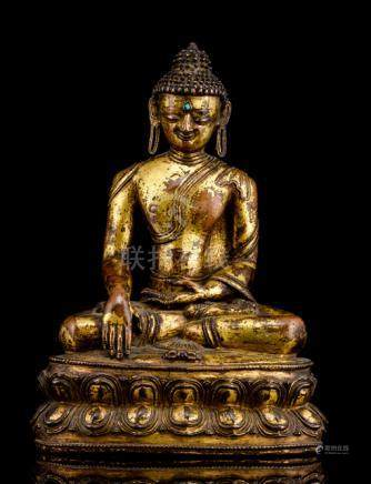 A GILT-BRONZE FIGURE OF BUDDHA SHAKYAMUNI, TIBET, 15th ct., seated in vajrasana on a lotus base with