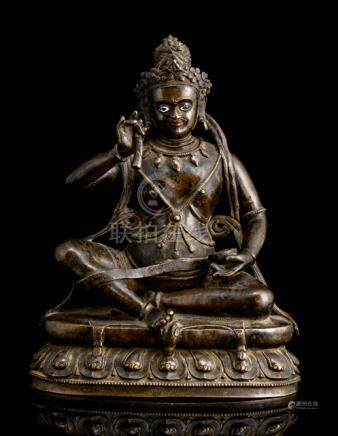 AN IMPORTANT BRONZE FIGURE OF THE MAHASIDDHA KRSHNACARIN, TIBET, late 15th ct., seated in rajalilasa
