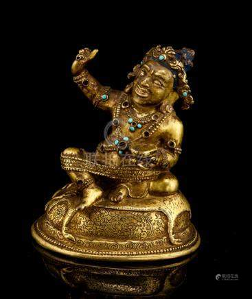 A FINE GILT-BRONZE FIGURINE OF THE MAHASIDDHA VIRUPA, TIBET, 16th ct., seated in rajalilasana on a c