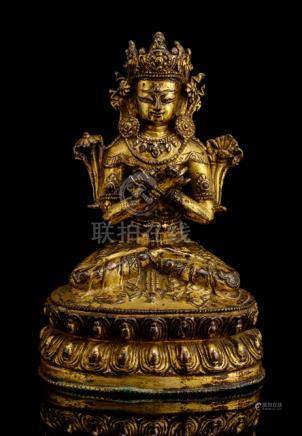 A GILT-BRONZE FIGURE OF VAJRADHARA, TIBET, 16th ct., seated in vajrasana on a lotus base with the ha