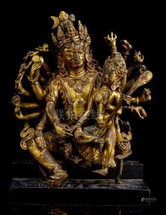 AN IMPORTANT GILT-BRONZE GROUP OF SHIVA AND PARVATI, NEPAL, 17th ct., on base. Seated in lalitasana,