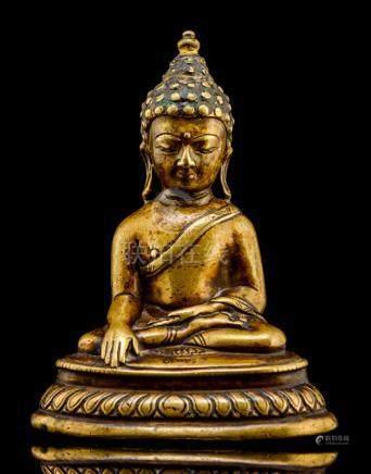 A BRONZE FIGURE OF BUDDHA SHAKYAMUNI, TIBET, ca. 14th ct., seated in vajrasana on a lotus base, its