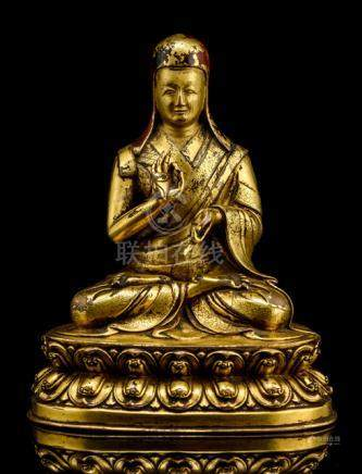 A FINE GILT-BRONZE FIGURE OF A SASKYAPA LAMA, TIBET, 15th/16th ct., seated in vajrasana on a lotus b