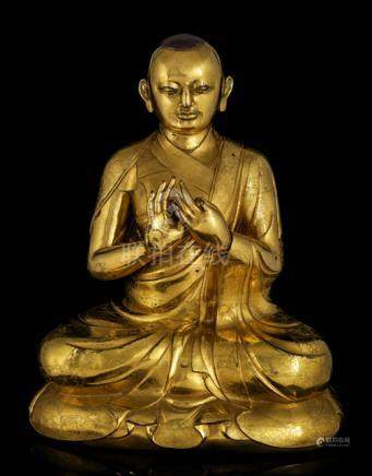 AN IMPORTANT GILT-BRONZE FIGURE OF A LAMA, TIBET, 17th ct., seated with legs crossed on a shaped pli