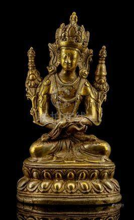 A GILT-BRONZE FIGURE OF VAJRADHARA, TIBET, 16th ct., seated in vajrasana on a lotus base with his ha