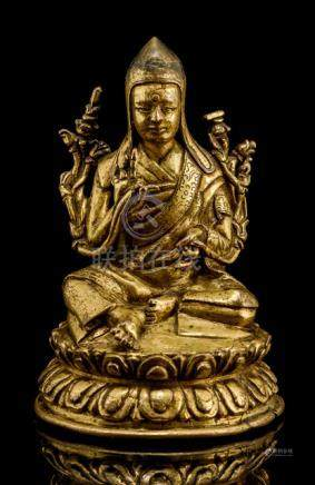 A GILT-BRONZE FIGURE OF A SASKYAPA LAMA, TIBET, 16th ct., seated in relaxed posture on a lotus base,