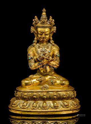 A GILT-BRONZE FIGURE OF VAJRADHARA, TIBET, 15th ct., seated in vajrasana on a lotus base with three