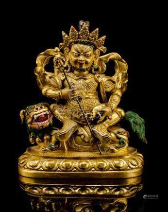 A GILT-BRONZE FIGURE OF VAISHRAVANA, TIBETO-CHINESE, 18th ct., seated astride his caparisoned lion r