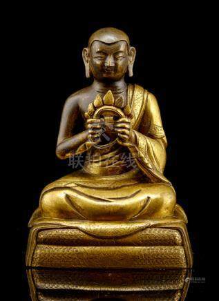 A PARCEL GILT-BRONZE FIGURE OF AN ARHAT, TIBETO-CHINESE, 18th ct., seated with legs crossed on a dou
