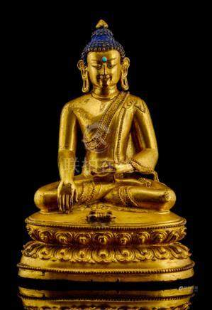 A GILT-BRONZE FIGURE OF BUDDHA SHAKYAMUNI, TIBET, 16th ct., seated in vajrasana on a lotus base with