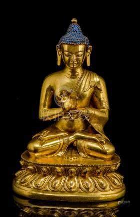 A GILT-BRONZE FIGURE OF BUDDHA SHAKYAMUNI ON A LOTUS BASE, Tibeto-Chinese, 18th ct. The Buddha seate