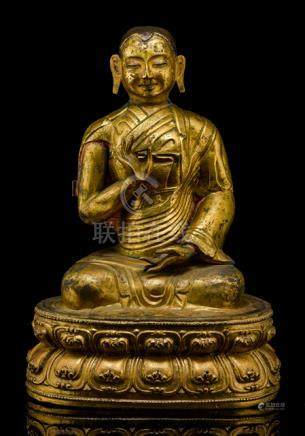 A GILT-REPOUSSÉ AND BRONZE FIGURE OF A LAMA, TIBETO-CHINESE, early 18th ct., seated with legs crosse