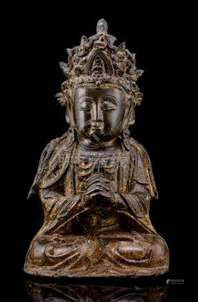 A BRONZE FIGURE OF GUANYIN, CHINA, 17th ct., seated in vajrasana on a plinth with both hands clasped