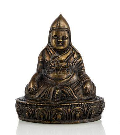 A BRONZE FIGURINE OF A LAMA, BHUTAN, 19th ct., seated with legs crossed on a lotus base, both hands